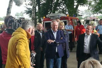 Stephan Weil steht neben Feuerwehr